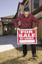Hispanic Man Placing For Sale Sign In Yard