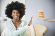 Mixed Race Woman Refusing Donuts