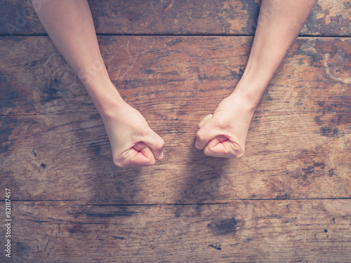 Female fists on a wooden table Canvas-taulu