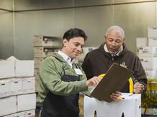 Workers Using Clipboard In Walk-in Freezer