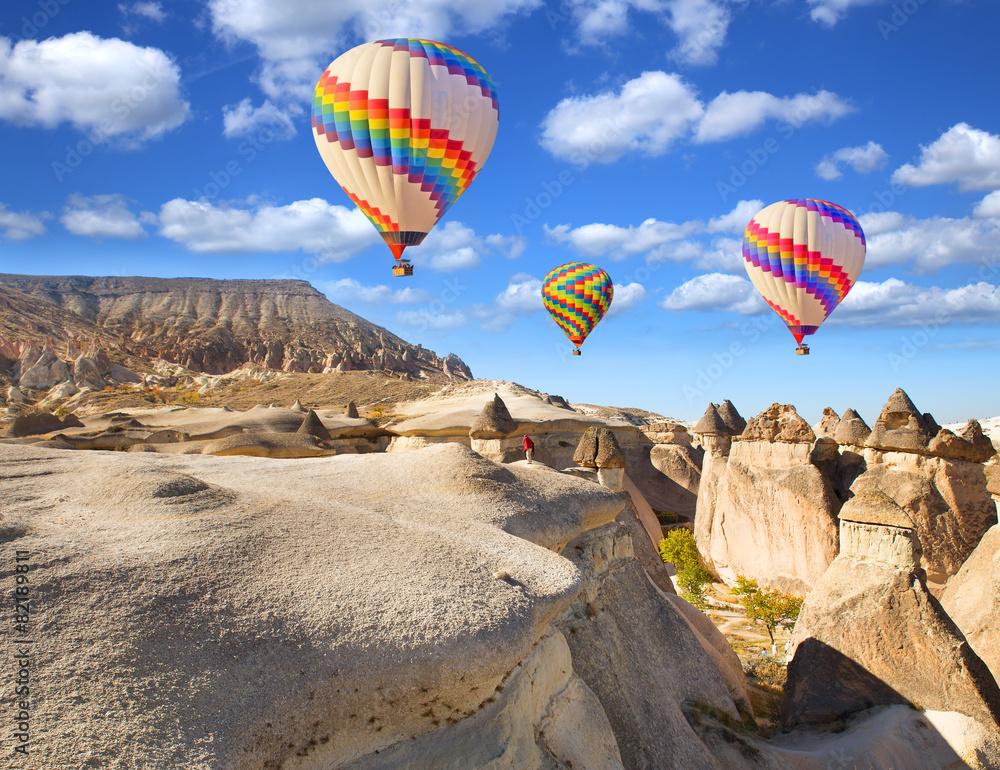 Fototapeta Hot air balloon flying over rock landscape at Cappadocia Turkey.
