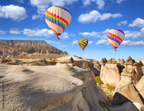 Papiers peints Montgolfière / Dirigeable Hot air balloon flying over rock landscape at Cappadocia Turkey.