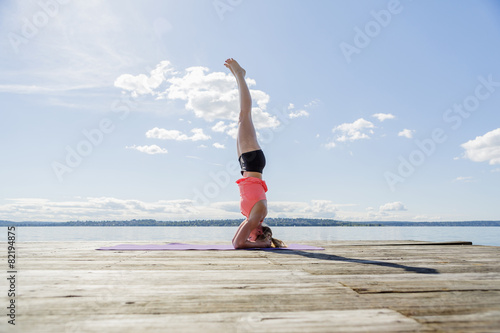 Woman practicing yoga on wooden jetty