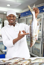 Mixed Race Grocer Preparing Fish In Market