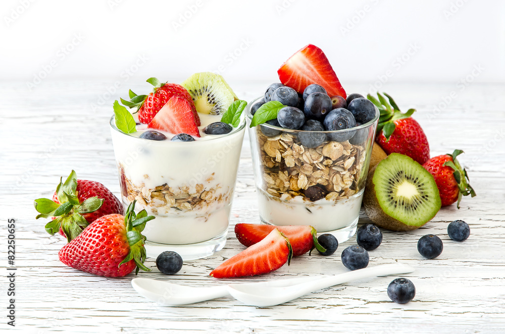 Fototapeta Healthy breakfast with muesli in glass, fresh berries and yogurt