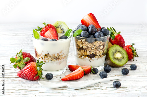 Obraz Healthy breakfast with muesli in glass, fresh berries and yogurt - fototapety do salonu