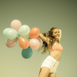 Girl jumping with colorful balloons on beach