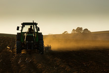 Tractor In Sunset Plowing The Field