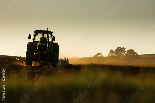 Tractor in sunset plowing the field плакат