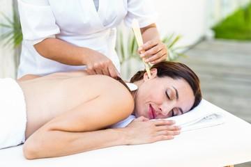 Obraz na płótnie Canvas Relaxed brunette getting an ear candling treatment