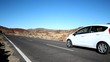Car drives by on empty raod in desert mountain landscape