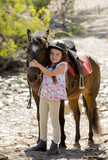 happy child girl with pony horse as young jockey in Summer