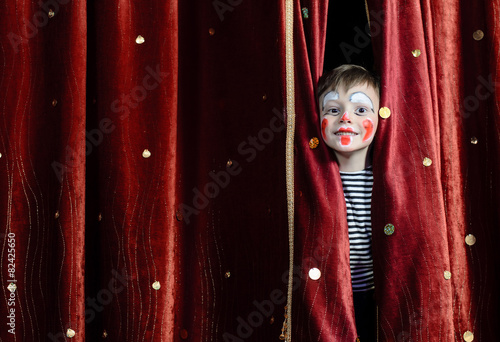 Fotografia Boy Clown Peering Through Stage Curtains