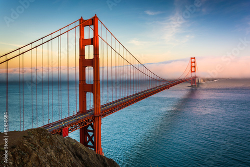 Sunset view of the Golden Gate Bridge and fog from Battery Spenc плакат