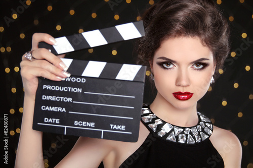 Fotografie, Obraz  Beautiful brunette woman model holding film clap board cinema. F
