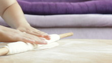 Rolling Out Dough On The Table With The Help Of A Rolling Pin
