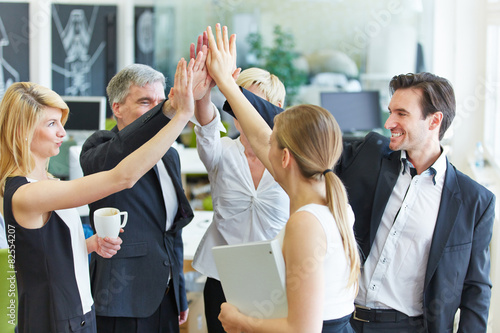 Obraz Business Team macht High Five im Büro - fototapety do salonu