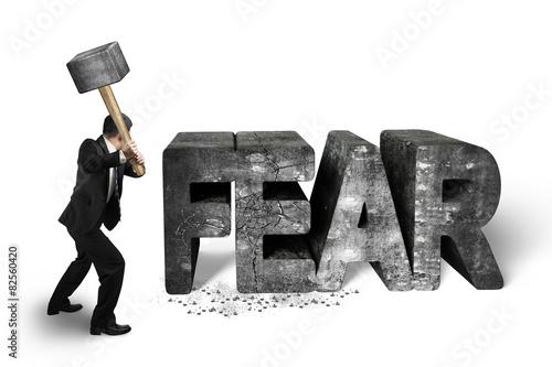Leinwand Poster Businessman holding sledgehammer hitting fear concrete word isol