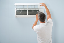 Man Cleaning Air Conditioning ...
