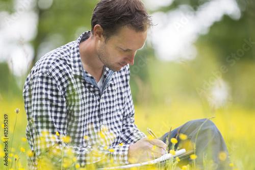 Fotografie, Obraz  Environmentalist Writing On Notepad In Park