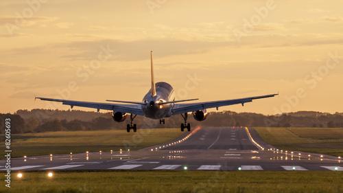 Staande foto Vliegtuig Lądowanie o zachodzie