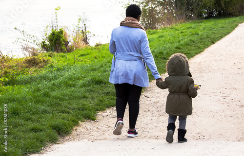 Fotografie, Obraz  Mother holding a hand of her daughter in spring day outdoors