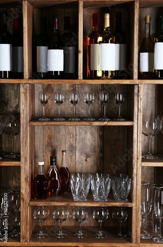 Spoed Foto op Canvas Bar Shelving with wine bottles with glasses on wooden wall background