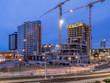 Construction cranes over Calgary at night.