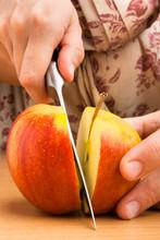 Hands Cutting An Apple Into Halves