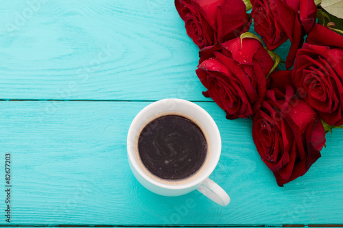 Fotografie, Tablou  Cup of coffee and red roses on blue wooden table. Top view