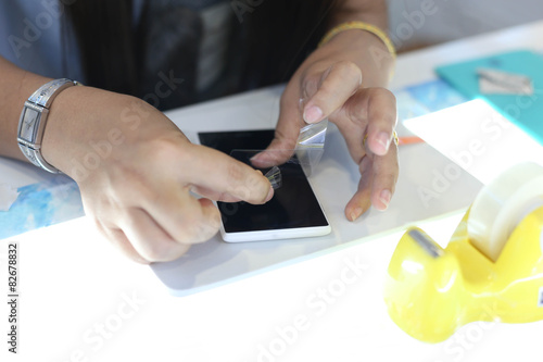 Foto  Woman applying a screen protector on an cellphone