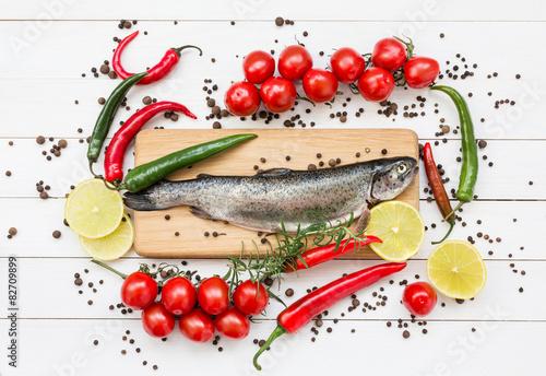 ryba-pstrag-na-drewnianej-desce-do-krojenia-z-pomidorami-koktajlowymi