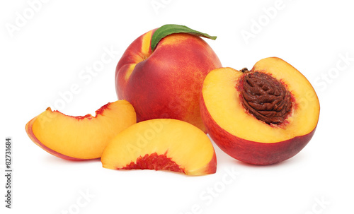 One whole and sliced nectarine with green leaf (isolated)