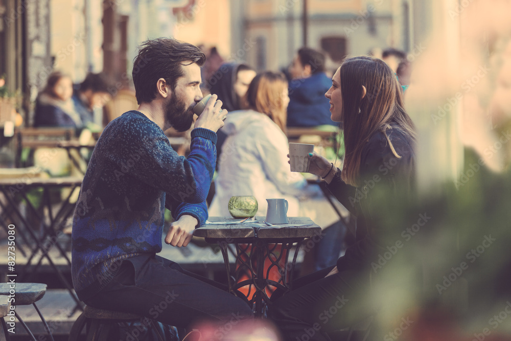 Fototapeta Hipster couple drinking coffee in Stockholm old town.