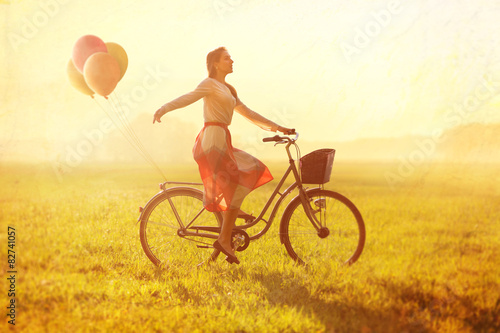 Fotografie, Obraz  Woman on a Bike with balloons