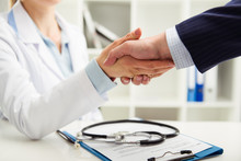 Woman Doctor Shaking Hand With...