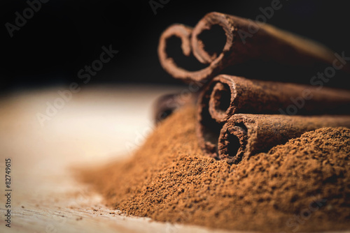 Fotografia Cinnamon sticks with cinnamon powder on wooden background