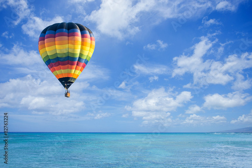Fotografia  Hot air balloon over ocean and clouds blue sky