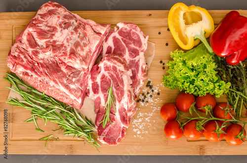 Staande foto Vlees Raw meat with vegetables and spices on wooden background