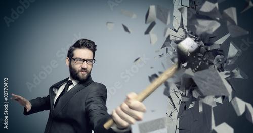 Fototapeta Young boss smashing a wall with a hammer