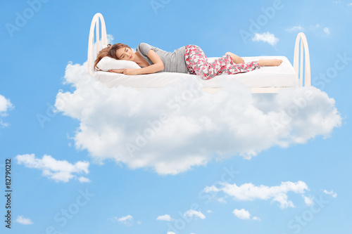 Fototapeta Woman sleeping on a comfortable bed in the clouds
