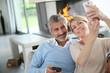 Mature couple at home having fun using smartphone
