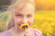 girl smells on a flower otudoor in grass