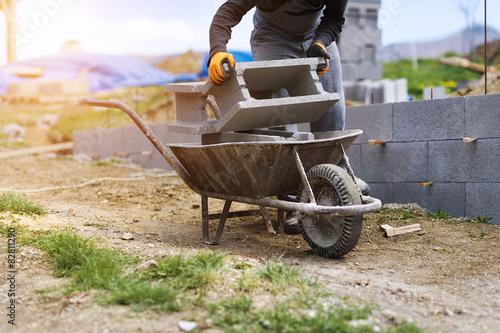 Tela Bricklayer taking another brick from a wheelbarrow