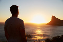 Silhouette Of Man Watching Sun Set Over Sea And Cliffs