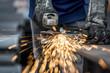 Leinwandbild Motiv Industrial worker cutting metal with many sharp sparks