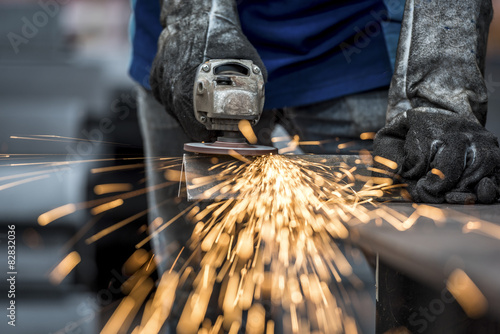 Türaufkleber Metall Industrial worker cutting metal with many sharp sparks