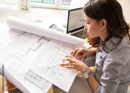 Photo Female architect working at home.She looking at blueprint.
