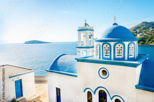 Edifice religieux Typical Greek blue dome of white church with sea view in sunny d