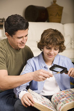 Hispanic Father And Son Examining Stamp Through Magnifying Glass